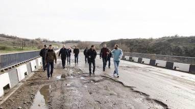 У Новобузькому районі дорогу на мосту через річку Інгул робітники вирішили відремонтувати вночі, укладаючи асфальт прямо в калюжі